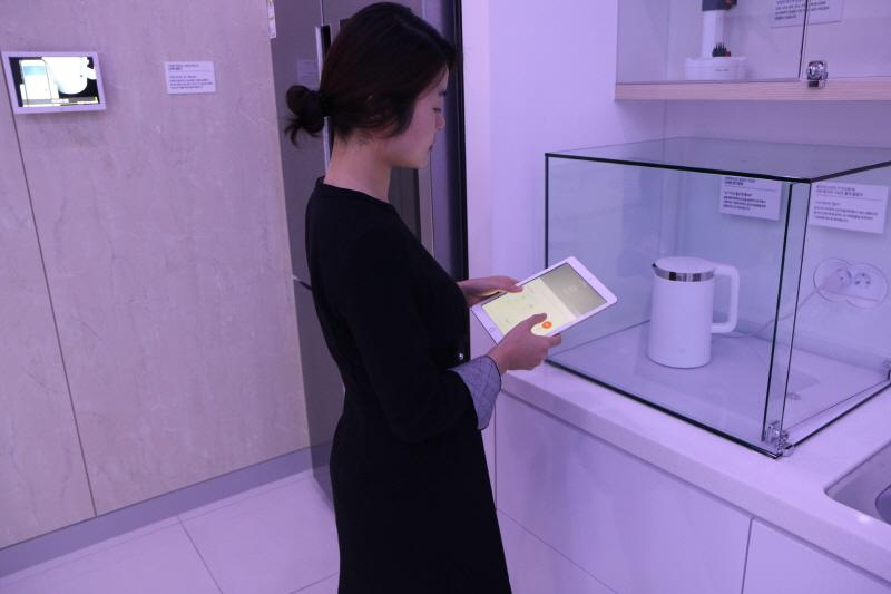 공보관실-성남시청 2층 종합홍보관 내 스마트홈 체험존에서 설정 온도에 맞춰 전기 포트의 물이 끓는지 확인 중이다