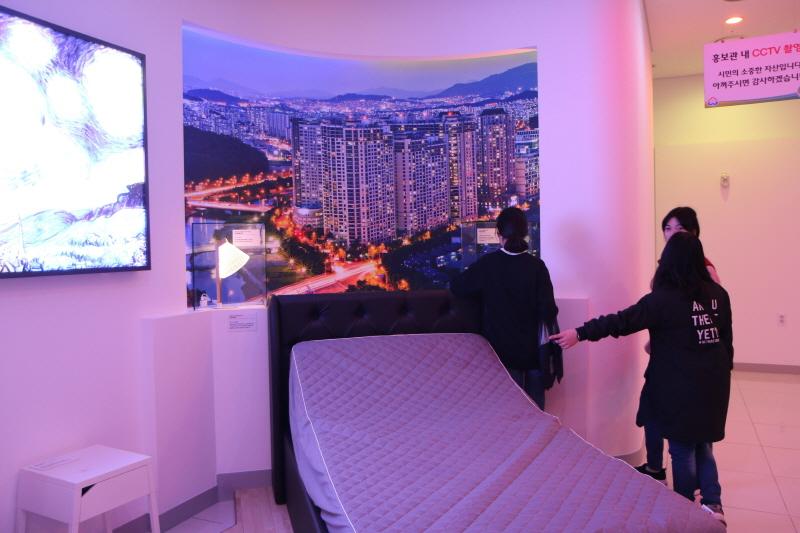 공보관실-성남시청 2층 종합홍보관 내 스마트홈 체험존에서 스마트폰으로 침대의 높낮이 원격 조정 중이다