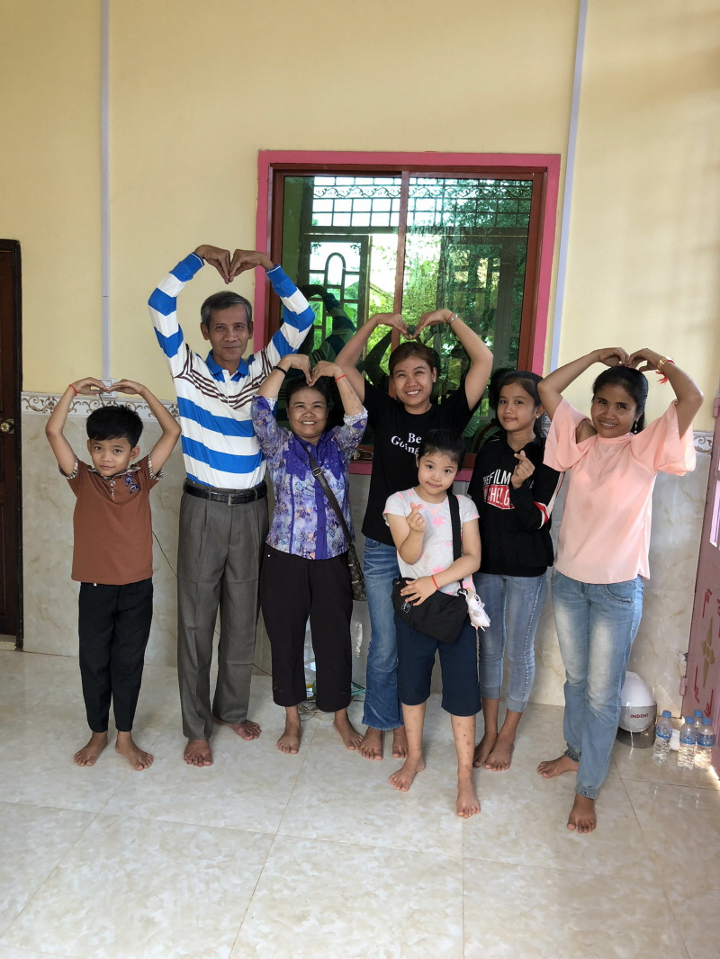 여성가족과-캄보디아 결혼이민자(가운데 검정 반팔티)가 지난해 10월 모국을 방문해 자신이 살던 집에서 가족들과 기념사진을 찍고 있다